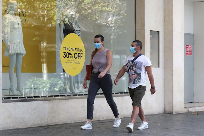 A couple is seen wearing masks while walking down Hay Street mall in Perth, Australia.