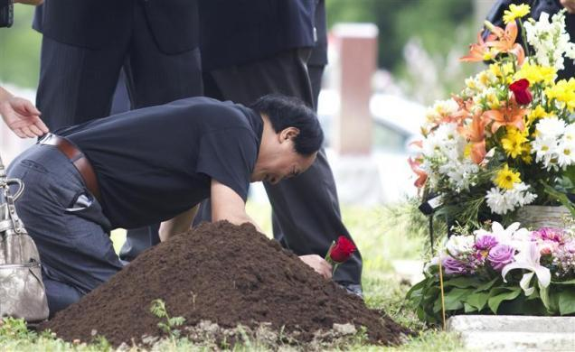 Dirang Lin, father of slain student Jun Lin lays a rose at his son's gravesite during funeral services in Montreal, July 26, 2012.