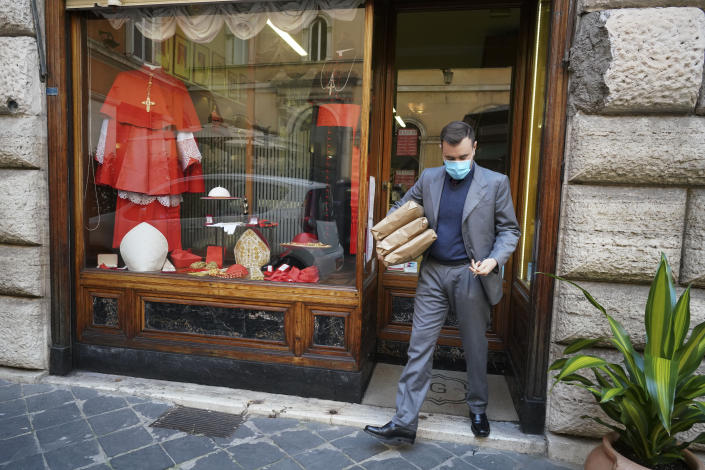 A shop attendant walks out of the Gammarelli clerical clothing shop, in Rome, Thursday, Nov. 26, 2020. The consistory to elevate new cardinals scheduled for Saturday, Nov. 28, in the time of coronavirus is like nothing the Holy See has ever seen. A handful of soon-to-be cardinals are in protective coronavirus quarantine, including African-American, Cardinal-designate Wilton Gregory, archbishop of Washington who explained that a U.S.-based ecclesiastical tailor took his measurements while he was still in Washington and sent them to Gammarelli, which then made them to order and sent them to Santa Marta hotel where he is undergoing the quarantine. (AP Photo/Andrew Medichini)