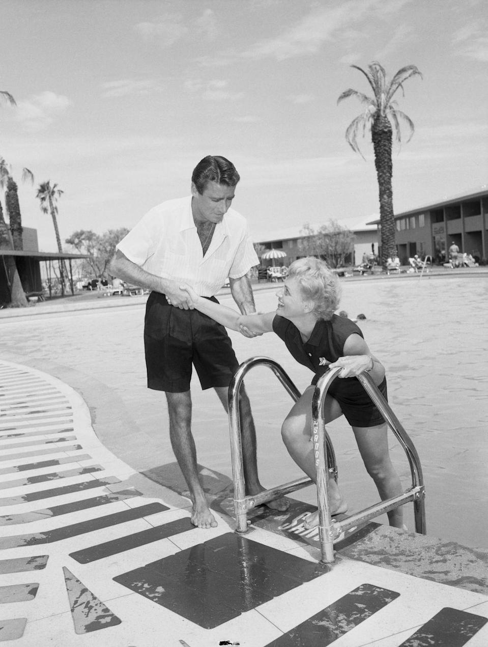 <p>Actors Peter Lawford and Judy Holliday by the pool of the Sands in 1953. The two were costars in the romantic comedy<em> It Should Happen to You</em>.</p>