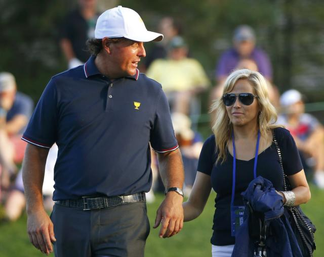 U.S. team member Phil Mickelson walks with his wife Amy after losing his first round match in the opening Four-ball matches for the 2013 Presidents Cup golf tournament at Muirfield Village Golf Club in Dublin, Ohio October 3, 2013. REUTERS/Jeff Haynes (UNITED STATES - Tags: SPORT GOLF)