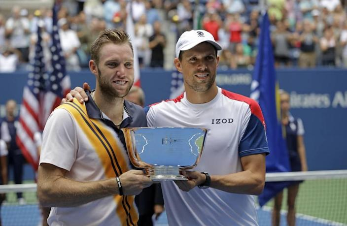 Jack Sock, left, and Mike Bryan hold the trophy after winning the men's doubles final at the 2018 U.S. Open. Sock led all pro players that year in doubles titles, but his singles game started to slide.
