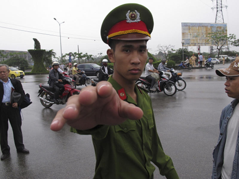 A Vietnamese police officer gestures toward a photographer, seeking to stop him from working close to a court in Haiphong Vietnam, Tuesday, April 2, 2013. A Vietnamese court begun hearing the trial of four fish farmers charged with attempted murder for fighting back against police and army officers seeking to evict them from their land last year. (AP Photo/Chris Brummitt)