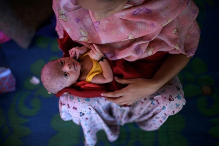 Johara Begum holds her five-day-old baby boy Mohammad Anas, who was delivered with the help of a neighbouring midwife, in the shelter she shares with her husband and family at the Jamtoli refugee camp near Cox's Bazar