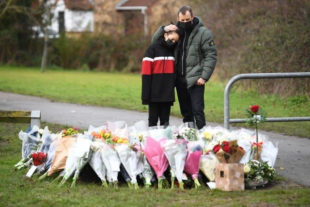 Two people look at flowers for Captain Sir Tom Moore