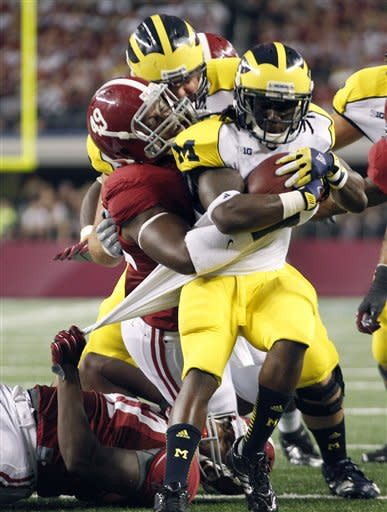 Michigan running back Vincent Smith (2) is stopped by Alabama linebacker Xzavier Dickson (47) and defensive lineman Ed Stinson (49) during the first half of an NCAA college football game at Cowboys Stadium in Arlington, Texas, Saturday, Sept. 1, 2012. (AP Photo/LM Otero)