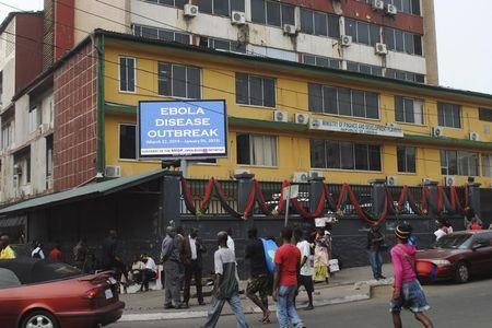 "Pedestrians walk past a sign reading ""Ebola disease outbreak"" outside the Ministry of Finance in Monrovia"