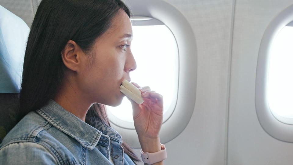 woman eating on airplane