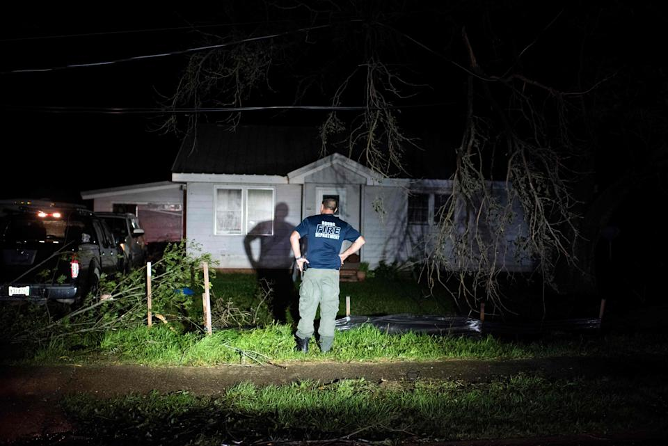 Bourg fire chief TJ Pellegrin asks a couple if they are okay after Hurricane Ida passed (Mark Felix/AFP via Getty Images)