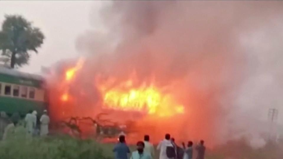 People watch fire burning a train after a gas canister passengers were using to cook breakfast exploded, near the town of Rahim Yar Khan in the south of Punjab province, Pakistan October 31, 2019, in this still image take from video. REUTERS/Asghar Bhawalpuri/via REUTERS TV