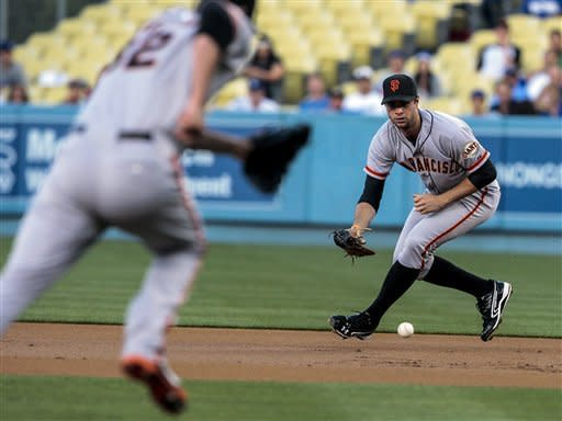 San Francisco Giants first baseman Brandon Belt makes a play on a ground ball during the first inning of a baseball game, Tuesday against the Los Angeles Dodgers, May 8, 2012, in Los Angeles. (AP Photo/Bret Hartman)