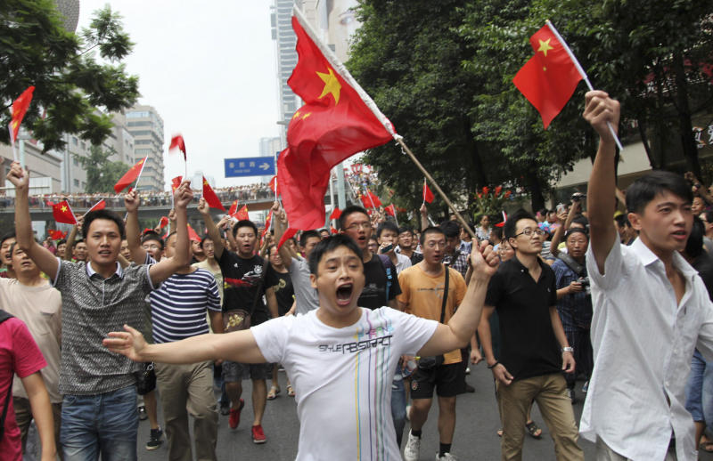 FILE - In this Aug. 19, 2012 file photo protesters wave Chinese national flags while marching against Japan's claim to islands which are also claimed by China, in Chengdu, in southwestern China's Sichuan province. The disputed ownership of these tiny constellations of islands is inflaming nationalist fervor from the cold North Pacific to the tropical South China Sea. In recent weeks, these long-simmering tensions have returned to a boil, with violent protests in Chinese cities, a provocative island junket by South Korea's lame-duck president, and Japan's government reportedly planning to buy disputed islands from their private owners. (AP Photo/File) CHINA OUT