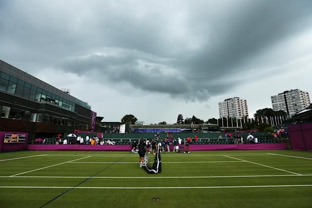LONDON, ENGLAND - JULY 29: Members of the groundstaff remove the net on a court as rain delays play on Day 2 of the London 2012 Olympic Games at the All England Lawn Tennis and Croquet Club in Wimbledon on July 29, 2012 in London, England. (Photo by Ezra Shaw/Getty Images)
