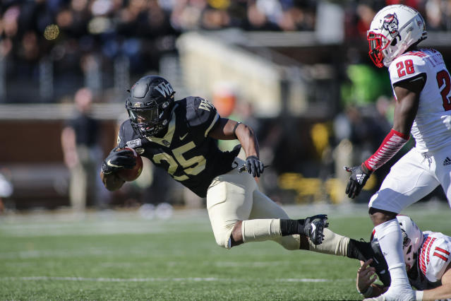 Wake Forest running back Kenneth Walker, left, tries to break free of a shoestring tackle by North Carolina State linebacker Payton Wilson (11) as cornerback Kishawn Miller looks on in the first half of an NCAA college football game in Winston-Salem, N.C., Saturday, Nov. 2, 2019. (AP Photo/Nell Redmond)