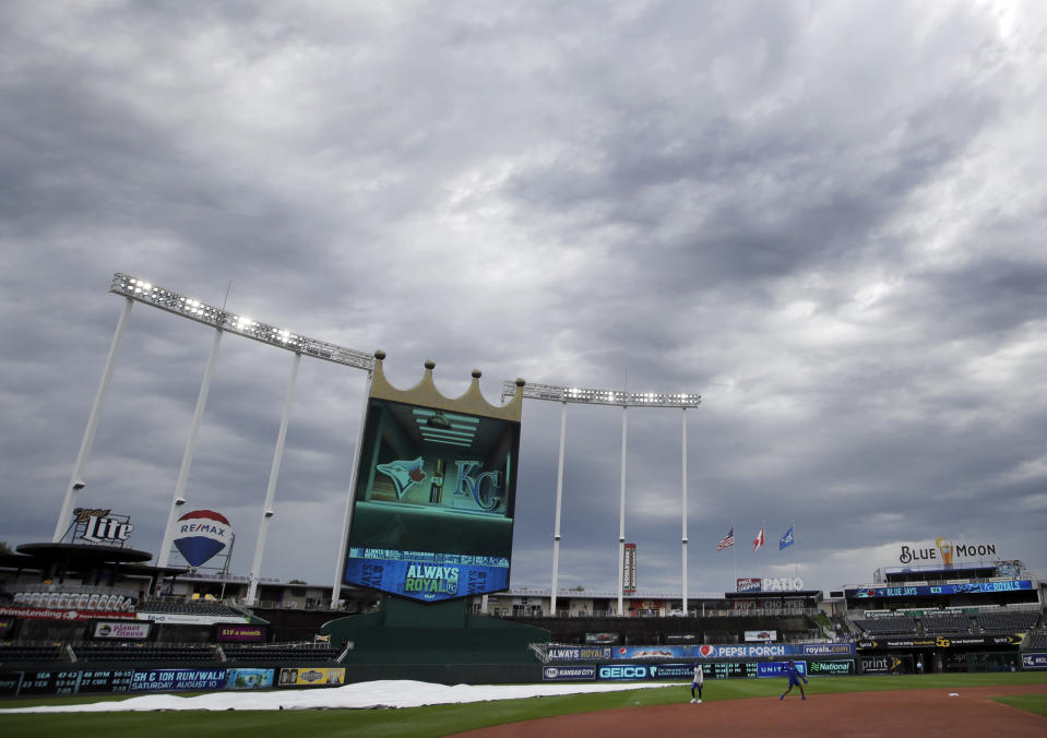 Players warm up as the rain cover is removed from the infield before a baseball game between the Kansas City Royals and the Toronto Blue Jays at Kauffman Stadium in Kansas City, Mo., Wednesday, July 31, 2019. (AP Photo/Orlin Wagner)
