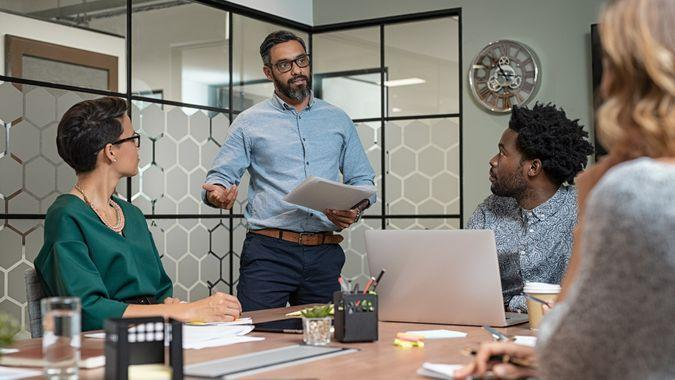 Confident mature businessman giving a presentation to his team in office.