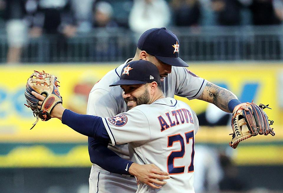 Jose Altuve and Carlos Correa celebrate after the Astros defeat the White Sox 10-1 to win Game 4.