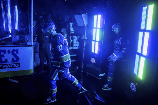 Vancouver Canucks' Daniel Sedin, left, and his twin brother, Henrik Sedin, both of Sweden, walk onto the ice to play in their last home NHL hockey game, against the Arizona Coyotes on Thursday, April 5, 2018, in Vancouver, British Columbia. (Darryl Dyck/The Canadian Press via AP)
