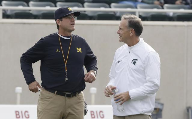 In this Oct. 29, 2016 photo, Michigan head coach Jim Harbaugh (L) greets Michigan State head coach Mark Dantonio before their game in East Lansing, Michigan. (AP Photo/Carlos Osorio, File)