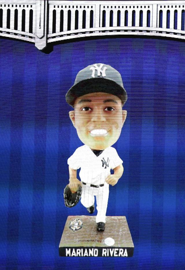 An image of a Mariano Rivera bobblehead doll is displayed on the scoreboard during a baseball game between the New York Yankees and the Tampa Bay Rays, Tuesday, Sept. 24, 2013, in New York. The Yankees were forced to hand out vouchers for the giveaway honoring the career saves leader to the first 18,000 fans who arrived for the game, because of a transportation issue. A public address announcement in the bottom of the third inning said the bouncy figurines were now available to be picked up. (AP Photo/Kathy Willens)