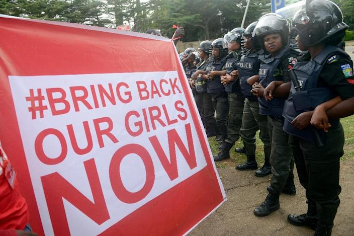 Supporters of the #BringBackOurGirls campaign hold a placard in front of a police blockade (AFP Photo/Pius Utomi Ekpei)