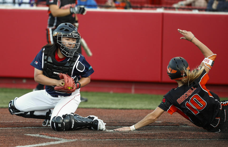 Sammy Marshall of Chicago Bandits scores a run ahead of the tag from Xu Junyi of Beijing Shougang Eagles during a National Pro Fastpitch League softball game. (Xinhua/Joel Lerner via Getty Images)