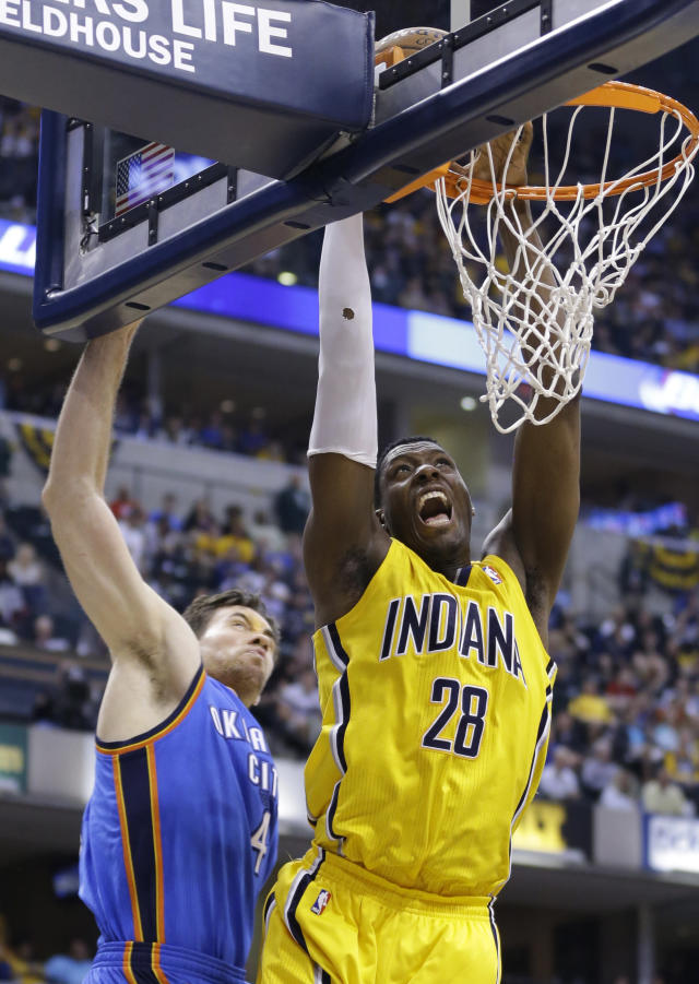 Indiana Pacers center Ian Mahinmi (28) gets a basket on a dunk in front of Oklahoma City Thunder forward Nick Collison in the second half of an NBA basketball game in Indianapolis, Sunday, April 13, 2014. The Pacers defeated the Thunder 102-97. (AP Photo/Michael Conroy)