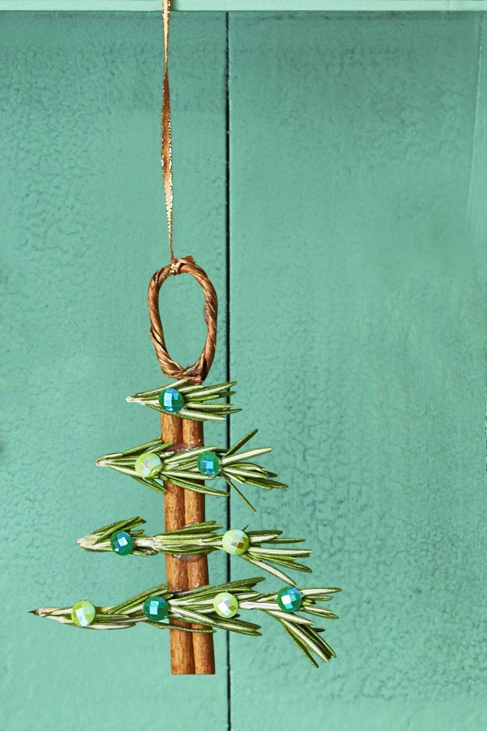 "<p>Not only does this easy-to-craft ornament look pretty, but it also smells great! Hot glue brings together rosemary, cinnamon sticks, and gemstones for a festive and eye-catching final look.</p><p><strong>To make:</strong> Bend a 30"" piece of naturally coiled wrapped wire in half to form a loop, then gently push each end into the hollow part of a cinnamon stick. Use hot glue to attach cut sprigs of fresh rosemary for branches and small gems for ornaments. </p><p><strong><a class=""link rapid-noclick-resp"" href=""https://www.amazon.com/s?k=cinnamon+stick&i=grocery&ref=nb_sb_noss&tag=syn-yahoo-20&ascsubtag=%5Bartid%7C10050.g.1070%5Bsrc%7Cyahoo-us"" rel=""nofollow noopener"" target=""_blank"" data-ylk=""slk:SHOP CINNAMON STICKS"">SHOP CINNAMON STICKS</a><br></strong></p>"