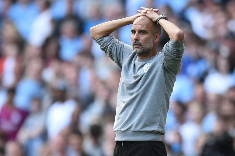 Pep Guardiola's Manchester City are three points behind the Premier League leaders (AFP/Oli SCARFF)