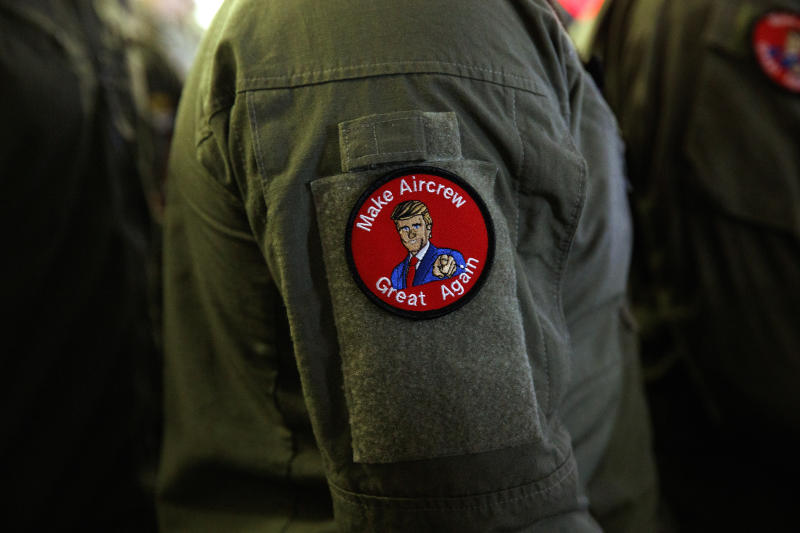 """A service member wears a patch that says """"Make Aircrew Great Again"""" as they listen to President Donald Trump speak to troops at a Memorial Day event aboard the USS Wasp, Tuesday, May 28, 2019, in Yokosuka, Japan. The patch includes a likeness of Trump. (AP Photo/Evan Vucci)"""