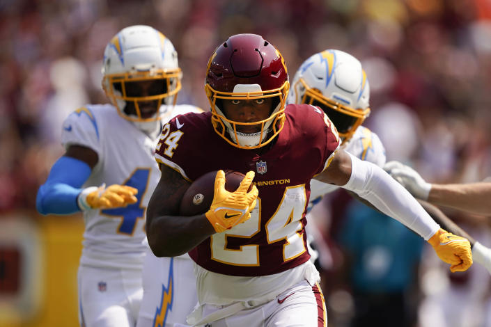 Washington Football Team running back Antonio Gibson (24) runs with the ball against the Los Angeles Chargers during the first half of an NFL football game, Sunday, Sept. 12, 2021, in Landover, Md. (AP Photo/Andrew Harnik)
