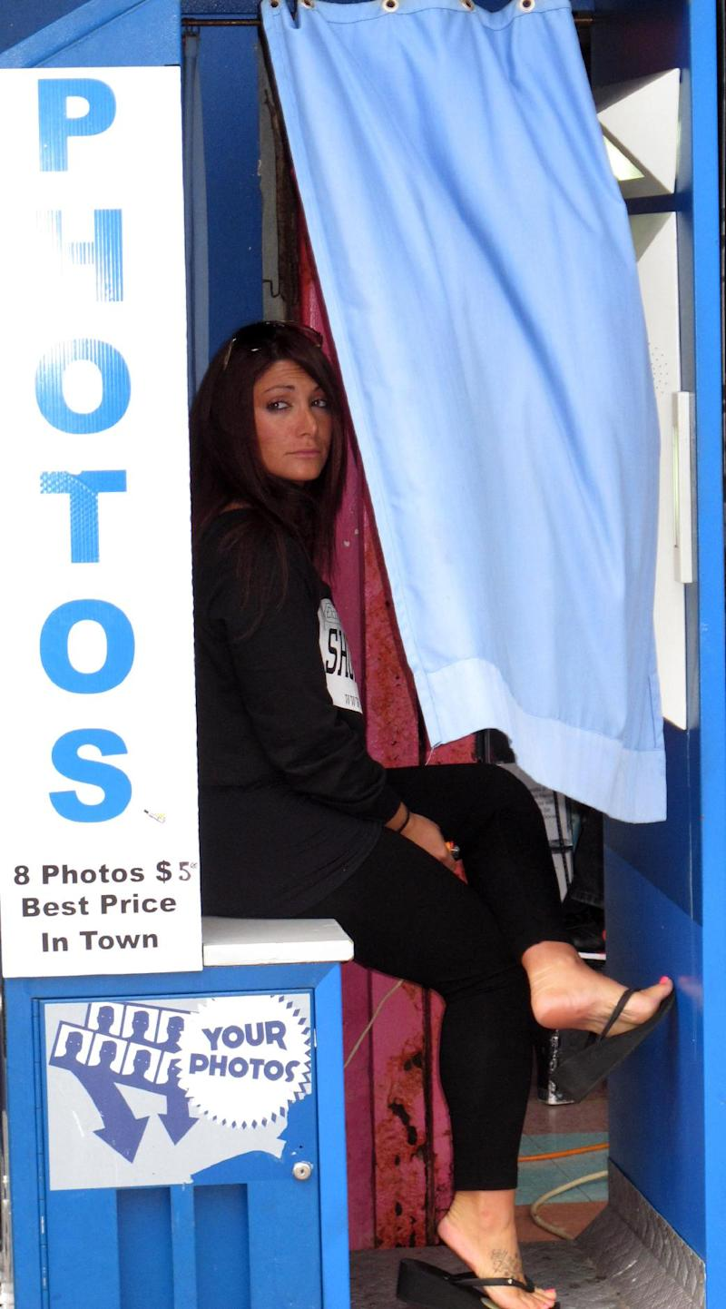 """This June 14, 2012 photo shows Deena Cortese, a cast member of MTV's """"Jersey Shore"""" series, sitting in a photo booth smoking a cigarette while filming an episode of the show in Seaside Heights, N.J. Cortese has a municipal court date next month for a disorderly persons charge for allegedly dancing in the street and interfering with traffic. (AP Photo/Wayne Parry)"""