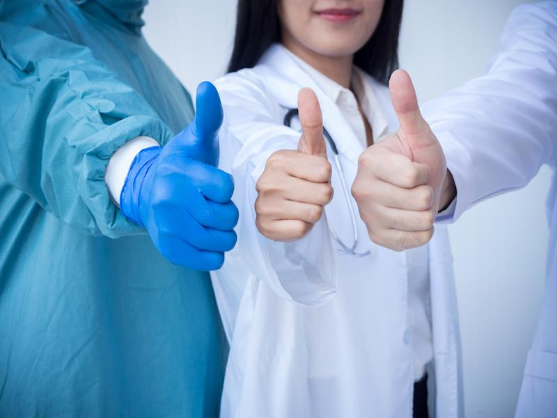 Three healthcare providers from different fields with their thumbs up.