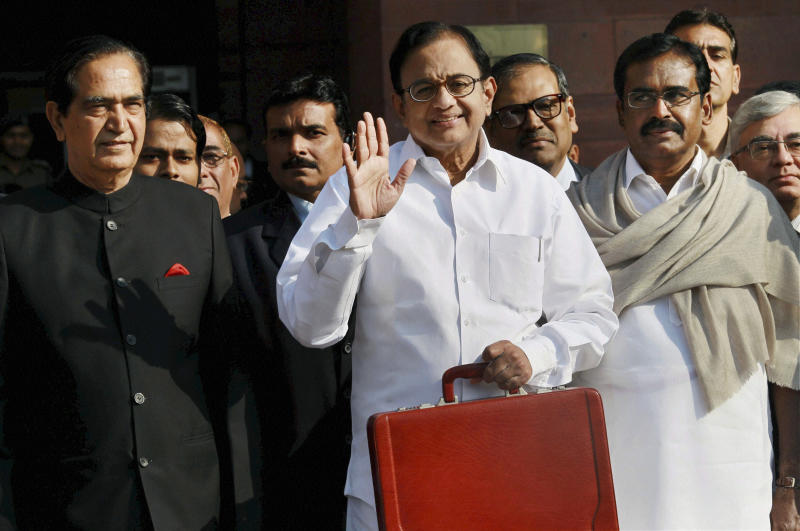 Indian Finance Minister Palaniappan Chidambaram waves to the media outside the Finance Ministry as he leaves for Parliament to present the annual budget in New Delhi, India, Thursday, Feb. 28, 2013.  Chidambaram unveiled a national budget with a promise to put Asia's third largest economy back on a path of high growth and to check runaway inflation and the fiscal deficit. (AP Photo)