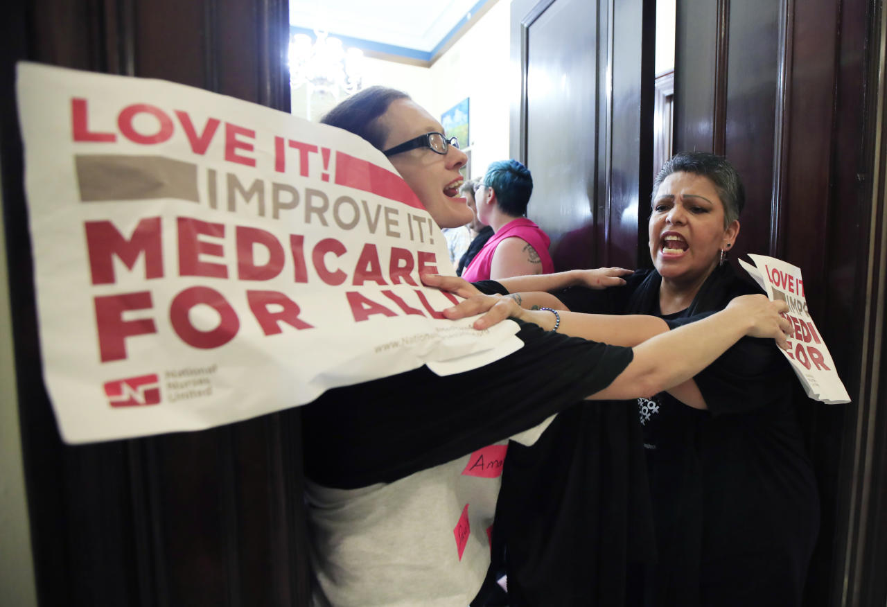 Protesters against the Republic health care proposals block the entrance to the office of Sen. Cory Gardner, R-Colo., at the Russell Senate Office building on Capitol Hill in Washington, Wednesday, July 19, 2017. (AP Photo/Manuel Balce Ceneta)