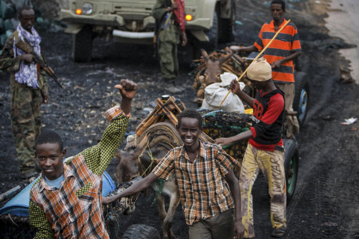 In this photo released by the African Union-United Nations Information Support Team, a Somali youth gestures as he pulls a donkey-drawn water cart past sacks of charcoal while a convoy of Kenyan soldiers serving with the African Union Mission in Somalia (AMISOM) passes by, in Kismayo, southern Somalia, Tuesday, Oct. 2, 2012. Allied African troops have taken full control of Kismayo in Somalia, the last stronghold of al-Shabab Islamist rebels who have been fighting against the country's internationally backed government, a Kenyan military official said Tuesday, and Kenya Defence Forces and the Somali National Army are now patrolling the streets. (AP Photo/AU-UN IST, Stuart Price)