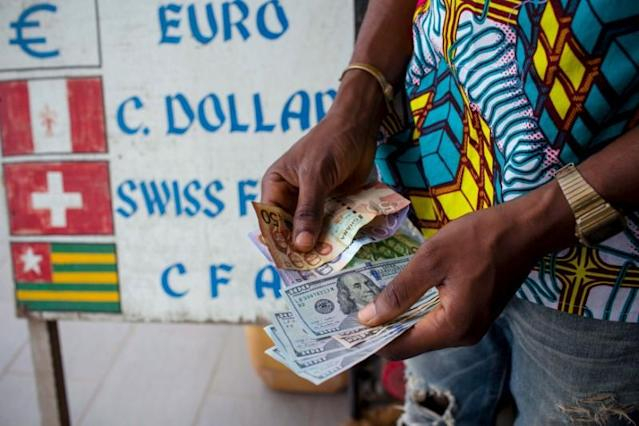 FILE PHOTO: A man trades U.S. dollars for Ghanaian cedis at a currency exchange office in Accra, Ghana, June 15, 2015. REUTERS/Francis Kokoroko/File Photo