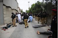 EDITORS NOTE: Graphic content / Police collect evidence next to the bodies of alleged gunmen outside the Pakistan Stock Exchange building in Karachi on June 29, 2020. - A group of gunmen attacked the Pakistan Stock Exchange in Karachi June 29, police said, with four of the attackers killed. (Photo by Asif HASSAN / AFP) (Photo by ASIF HASSAN/AFP via Getty Images)
