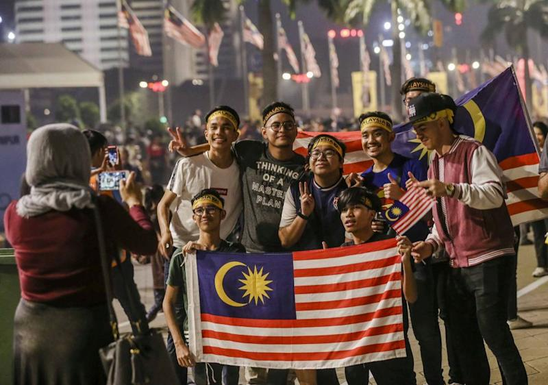 People pose for a picture with the Jalur Gemilang at Dataran Merdeka, Kuala Lumpur to celebrate Malaysia's 61st anniversary August 30, 2018. — Picture by Firdaus Llatif
