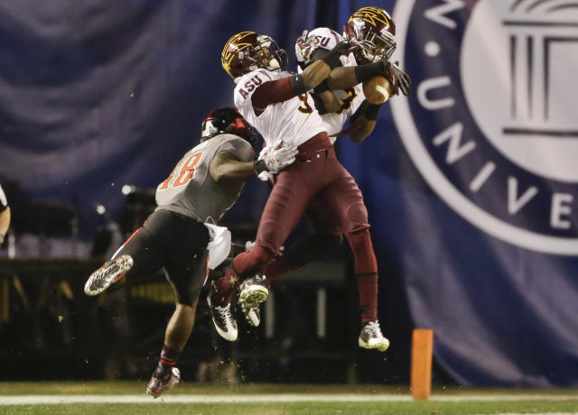 Arizona State defensive backs Robert Nelson, left, and Damarious Randall battle for a long pass intended for Texas Tech wide receiver Eric Ward during the first half of the Holiday Bowl NCAA college football football game Monday, Dec. 30, 2013, in San Diego. (AP Photo/Lenny Ignelzi)