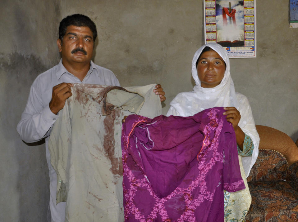 Pastor Haroon Sadiq Cheeda and his wife Mariam Haroon, who were beaten along with their son by Muslim neighbors and told to leave their village, show their blood-stains clothes, in a village in Rahim Yar Khan district, Pakistan, Monday, July 6, 2020. Analysts and activists say minorities in Pakistan are increasingly vulnerable to Islamic extremists as Prime Minister Imran Khan vacillates between trying to forge a pluralistic nation and his conservative Islamic beliefs. (AP Photo/Waleed Saddique)