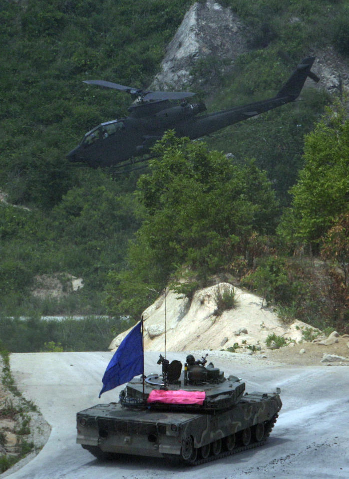 In this photo taken Tuesday, June 19, 2012, a South Korean Army's AH-1S Cobra flies over K1A1 tank during a South Korea-U.S. joint military live-fire drills at Seungjin Fire Training Field in Pocheon, South Korea, near the border with North Korea. The drills were held in a show of combat readiness ahead of the 62nd anniversary of the start of the Korean War on June 25. (AP Photo/Lee Jin-man)