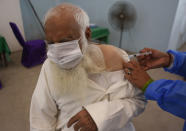 A man reacts while receiving a Sinopharm coronavirus vaccine from a health worker at a vaccination center in Lahore, Pakistan, Monday, March 29, 2021. (AP Photo/K.M. Chaudary)