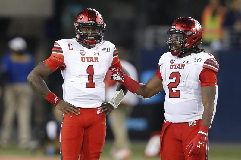 Utah quarterback Tyler Huntley (1) and Zack Moss (2) in the first half during an NCAA college football game against Arizona, Saturday, Nov. 23, 2019, in Tucson, Ariz. (AP Photo/Rick Scuteri)