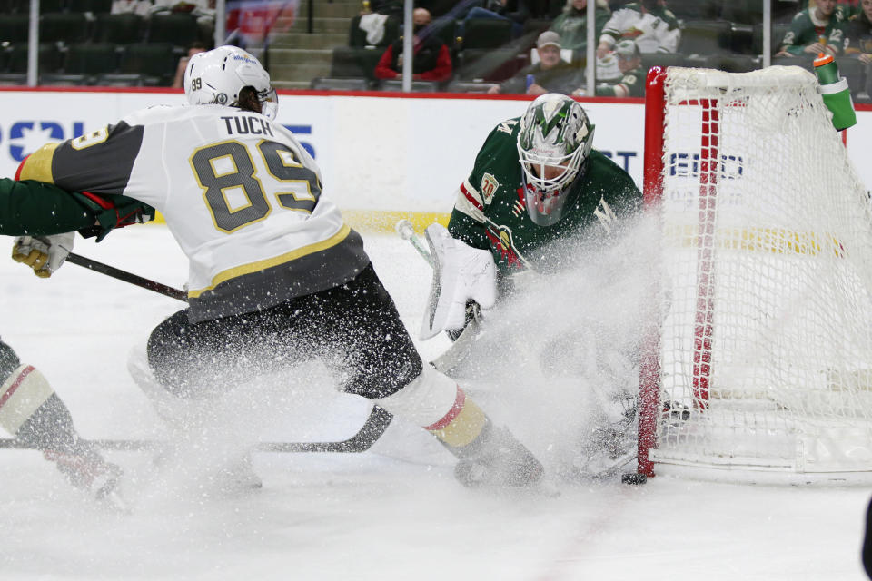 Minnesota Wild goaltender Cam Talbot (33) stops a shot by Vegas Golden Knights right wing Alex Tuch (89) during the second period in Game 6 of an NHL hockey Stanley Cup first-round playoff series Wednesday, May 26, 2021, in St. Paul, Minn. (AP Photo/Andy Clayton-King)