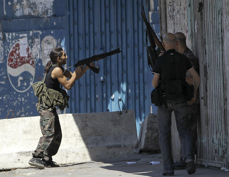 A Sunni gunman, left, fires by his AK-47 machine gun during clashes that erupted between pro and anti-Syrian regime gunmen in the northern port city of Tripoli, Lebanon, Friday, Aug. 24, 2012. The latest round of fighting first erupted on Monday in northern Lebanon and at least 15 have been killed in Tripoli this week and more than 100 have been wounded in fighting that is a spillover from Syria's civil war. (AP Photo/Hussein Malla)