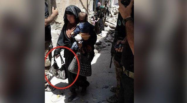 A chilling photo of a female suicide bomber holding her baby moments before she pressed the detonator has emerged. Photo: Al-Mawsleya TV