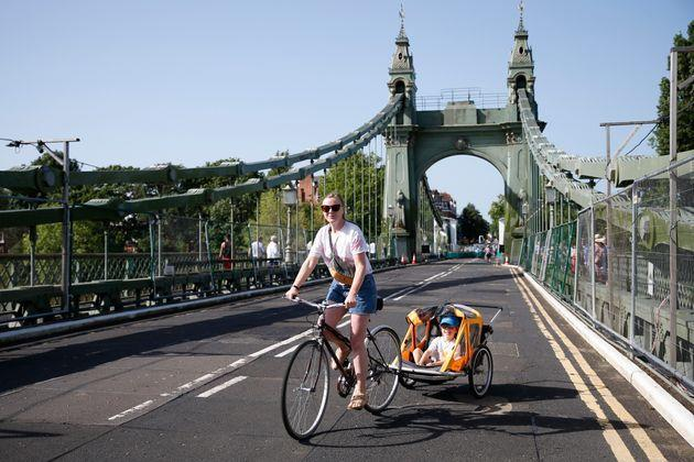 A cyclist rides over Hammersmith Bridge on July 17. The bridge was closed last year after cracks in the bridge worsened during a heatwave (Photo: Hollie Adams via Getty Images)