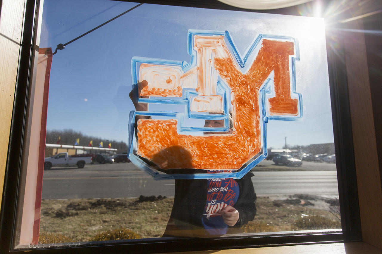 <p>Lauren Bengtzen, of Gilbertsville, Ky., paints the Marshall County High School logo on a window at a Taco John's restaurant in Benton, Ky., Thursday, Jan. 25, 2018. Bengtzen, who graduated from Marshall County High School last spring, said she came in early for her shift at the restaurant to paint the window after the fatal school shooting Tuesday. (Photo: Ryan Hermens/The Paducah Sun via AP) </p>