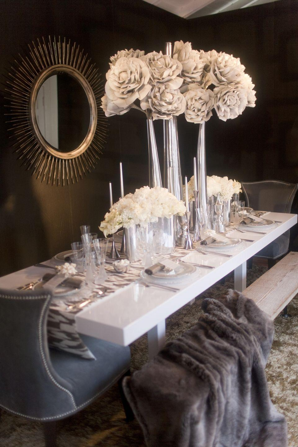 "<p>Tall centerpiece vases aren't just for weddings. Place large, white blooms in tall silver vases for a centerpiece that's frosted with the colors of a snowy winter. Side note: A furry throw on the chairs or benches will complement this design with a breath of warmth. </p><p><em>Via <a href=""http://www.sterlingsocial.com/"" rel=""nofollow noopener"" target=""_blank"" data-ylk=""slk:Sterling Social"" class=""link rapid-noclick-resp"">Sterling Social</a></em></p>"